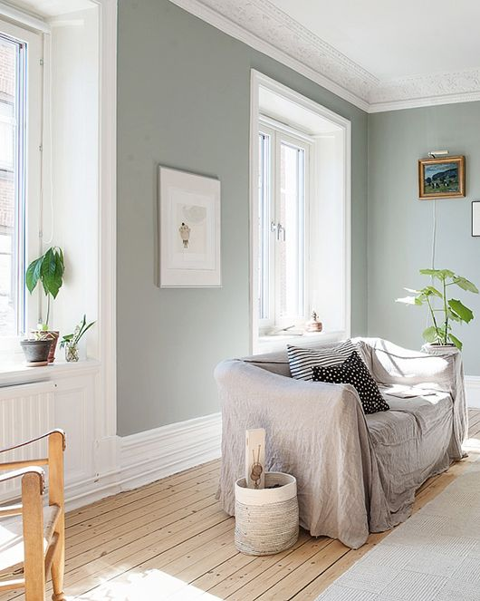 Soft aqua green walls in a pretty, light-filled apartment in Linnéstaden — a neighborhood in the central part of Gothenburg, sweden. built in 1885, it's been given a modern facelift — they've added modern furnishings and lighting fixtures, and painted it a calming shade of pale green that looks really fresh with all that light streaming in. but they've kept all those turn of the century details intact — wide double doors, the high ceilings and gorgeous crown moldings. #lightblue #paintcolors #farrowandball