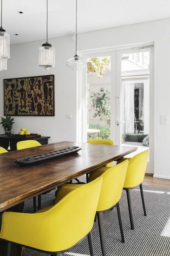 jolie salle à manger contemporaine avec chaises jaunes et table en bois massif