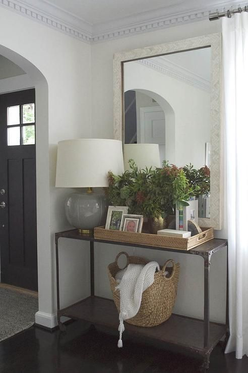 Gorgeous living room features an industrial console table filled with a gray lamp with brass ...