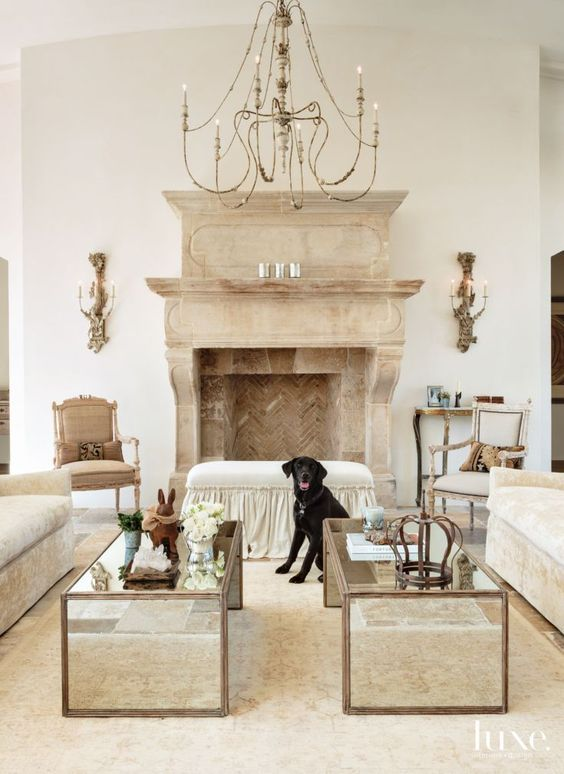 Traditional Cream Great Room with Antique Fireplace. Sconces from Paul Ferrante flank an antique fireplace from Exquisite Surfaces, adding a focal point to the great room. The couple's granddog, Koda, stands by a custom bench in Pindler fabric.