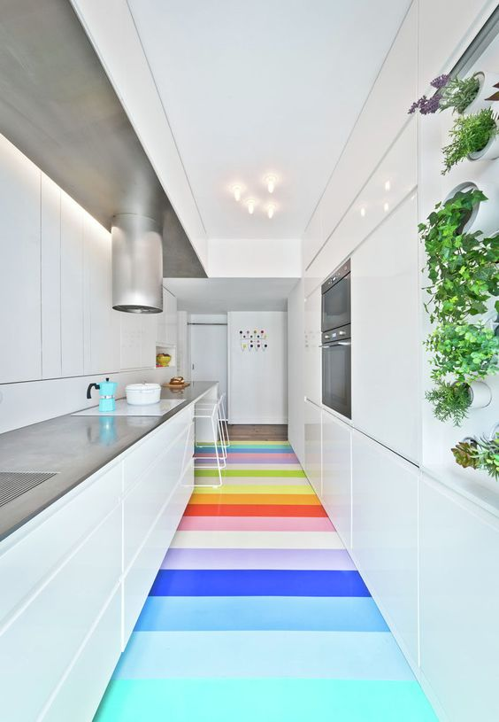 7 Examples Of Striped Floors In Contemporary Homes // 25 bright strips of natural rubber in 14 different colors add a whimsical touch to this modern kitchen and bring in some fun to the very white kitchen.