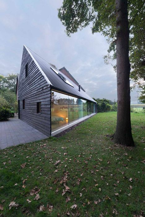 Blackened timber house with a triangular floor plan.: