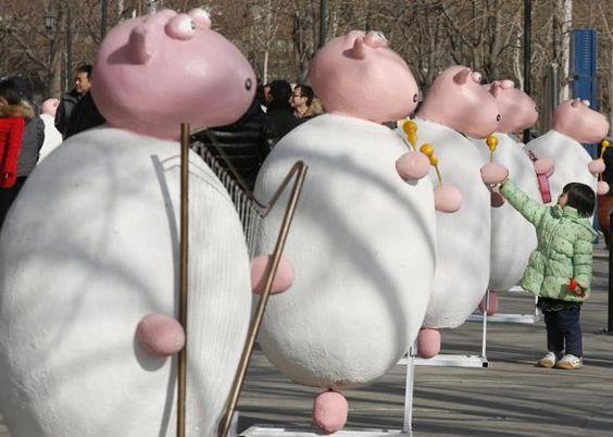 bimba gioca con pupazzi di pecore, sistemate in occasione del nuovo anno in #Cina: il #2015 secondo il calendario cinese sarà l'anno della #pecora