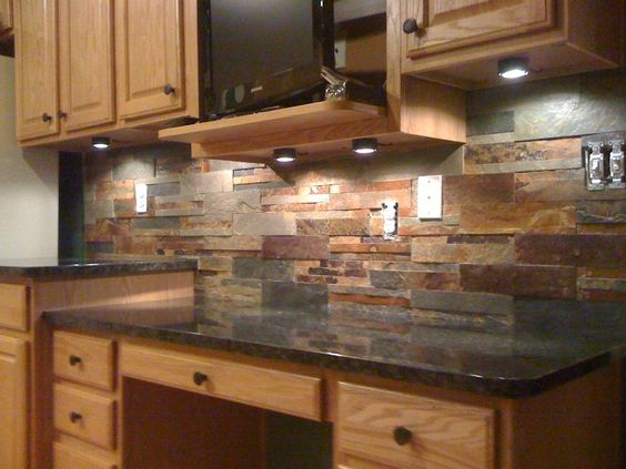 The nearly unfinished color of these cabinets looks great with the brick style backsplash but definitely with the dark countertops. It's a very 'opposites attract' type of balance.