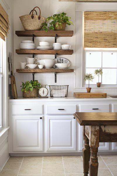 three heavy, open restaurant-style shelves holding a variety of plates and bowls, with straw baskets and a green plant on top, hung in a bright kitchen with white cabinets for the must-have, money-saving kitchen upgrades gallery: