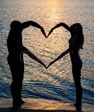 pareja joven haciendo forma de coraz n con los brazos en la playa frente a la puesta del sol de oro Foto de archivo