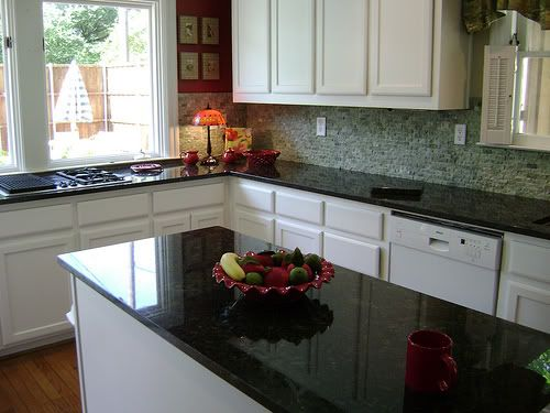 Custom kitchen with green granite countertops, island, dark brown cabinets  and mosaic tile backsplash