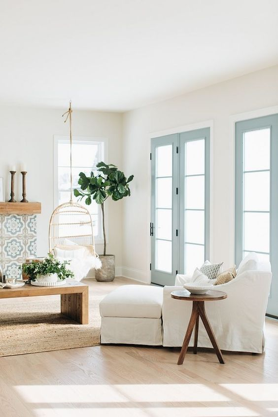 Hanging swing chairs a tiled fireplace surround light coastal decor and French Doors in James River Gray Benjamin Moore paint color #livingroom #livingroomdecor #coastaldecor #coastalstyle #BenjaminMooreJamesRiverGray #Frenchdoors #beachy #beachhouse