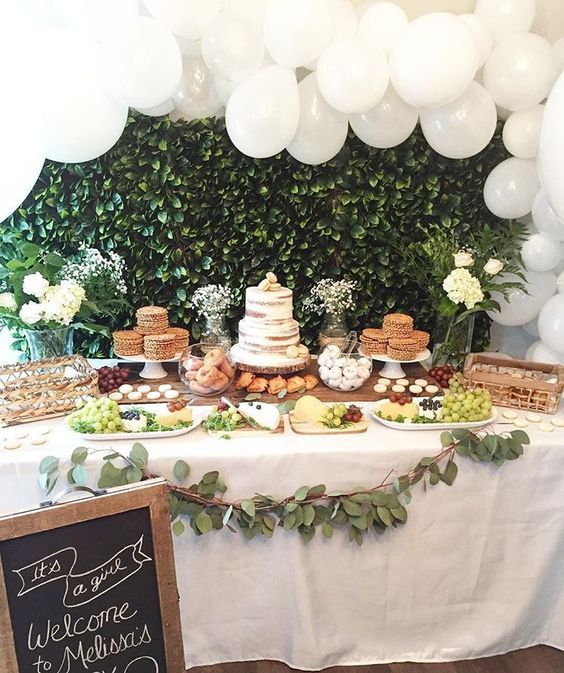 A Neutral Baby Shower Dessert Table With A Greenery Backdrop A