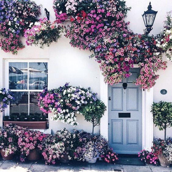 Fehér színű ház sok virággal