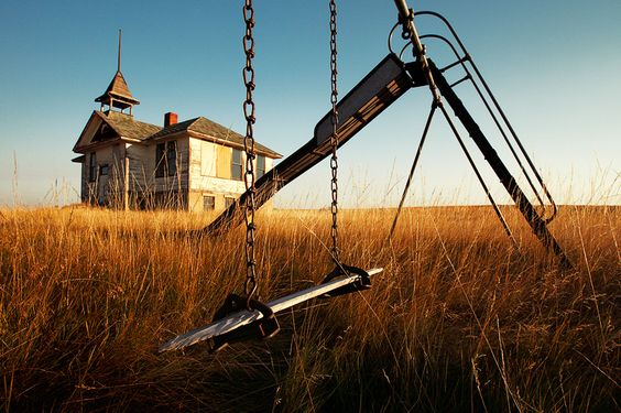 An old, abandoned schoolhouse and playground equipment in what was once Savoy, Montana.