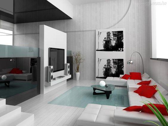 Abuso de preto e branco com o vermelho nas almofadas para quebrar os tons deixou o ambiente muito moderno.