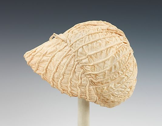 Dating from the first quarter of the 19th century, this infant cap provides a strong example of how infant clothing followed adult fashion forms. Even in traditional baby garments such as christening gowns, which share the characteristics of color, material and shape throughout the decades, it is possible to date the garments based upon the surface decoration or cut of the bodice, which often resemble adult styles. In this particular piece, the visor-like brim closely relates to the current…
