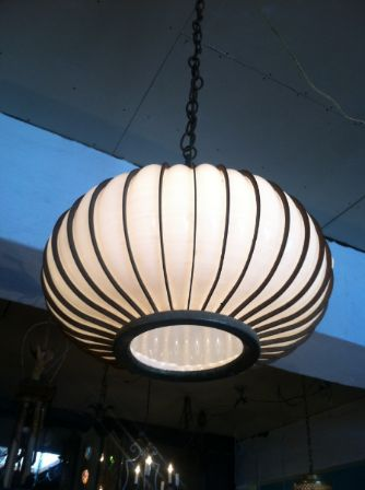 This mid-century Murano chandelier has a metal cage around the glass and a single bulb inside.