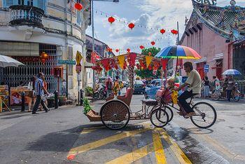 中華街なのに赤くない。ペナン島をはじめて訪れた人は、まずそう思うでしょう。 青空に映える淡い色あいの建物がならぶ通りを、ゆったりと通りすぎていく鮮やかなトライショー。競いあうように道路に突き出した中国語の看板に交じって、英語やタミル語、マレー語の看板も同じくらいたくさんあります。道端の屋台からは、嗅ぎ慣れないけど食欲をそそる匂いが漂ってきて、こっちへおいでと誘ってきます。