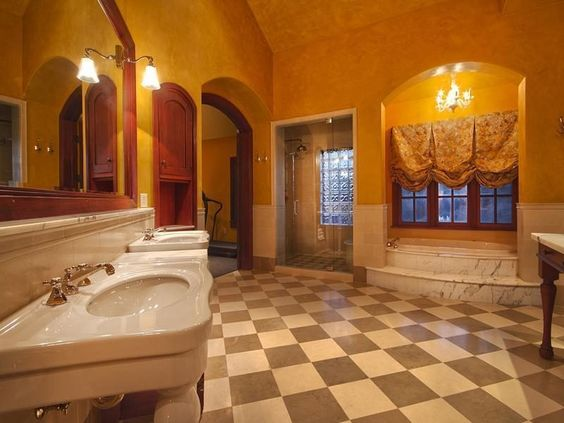 This Park City bathroom has checkered flooring, raised marble bathtub, arched openings, glass enclosed shower, hanging chandelier, floral curtains, and dual vanities.