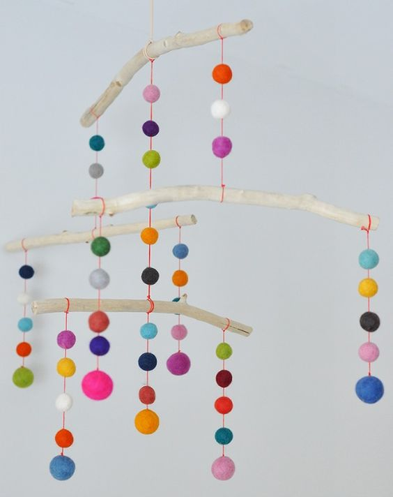 Colorful felted balls hang from wooden sticks. A great mobile for a kids room
