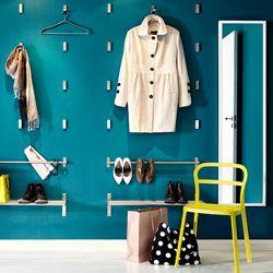Wand mit klappbaren BJÄRNUM Haken aus Aluminium, GRUNDTAL Stangen und GRUNDTAL Wandregalen in Edelstahl, REIDAR Stuhl in Gelb und STAVE Spiegel in Schwarzbraun