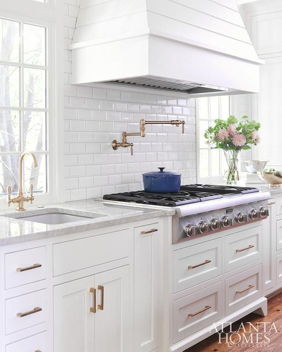 A white shiplap French hood is mounted to mini beveled subway backsplash tiles above a stainless steel cooktop placed atop white shaker pot and pan drawers accented with brass pulls complementing a vintage brass wing arm pot filler.