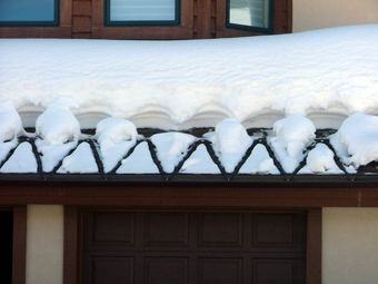 What are the benefits and drawbacks of using heat tape on gutters?