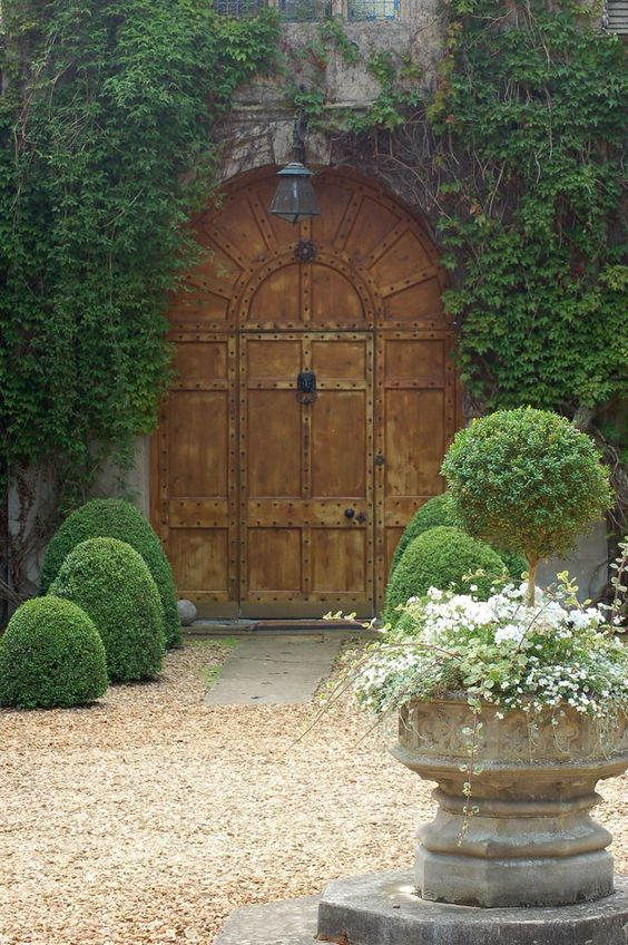 Garden gate ideas: Lovely landscaping surrounding arched garden gate doorway in French Country courtyard with boxood and gravel. #gardenideas #gardengate #FrenchCountry #Provence #courtyard #boxwood