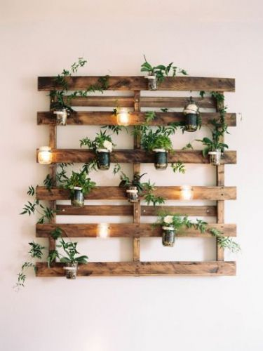 DIY Outdoor wall decor using a pallet, mason jars, candles and small plants.