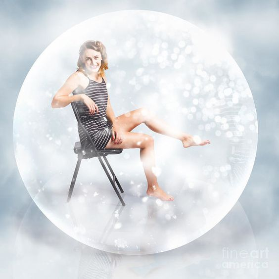 Creative fine art picture of a cute woman sitting inside a glass crystal ball under a seasonal fall of snow flakes. Snow globe pin up girl by Ryan Jorgensen