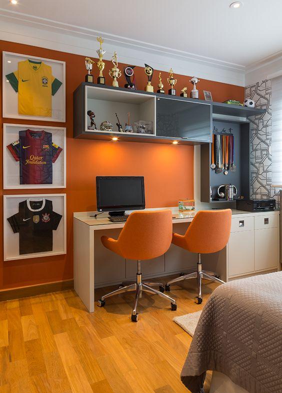 Super descolado esse quarto de adolescente. Lugar para todos os troféus e medalhas. A parede laranja deu um contraste com os  armários em tons de cinza. Projeto byfilomenaevaz  #quartodemenino #bancadadeestudo #quartocolorido