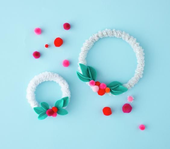 Mini Wreaths Wrap pipe cleaners around an embroidery hoop and embellish with pom poms and felt leaves.: