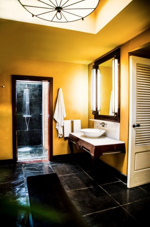 A skylight illuminates the shower in the suites at La Plantation d'Albion, where Mauritian design prevails. Golden walls creating a vibrant yet relaxing atmosphere.