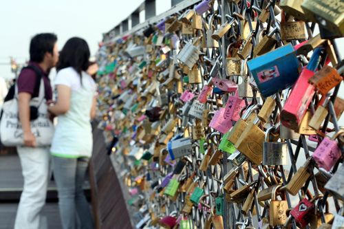 Couples place personalized locks on the Seoul Tower, then throw the keys away to symbolize forever. <3