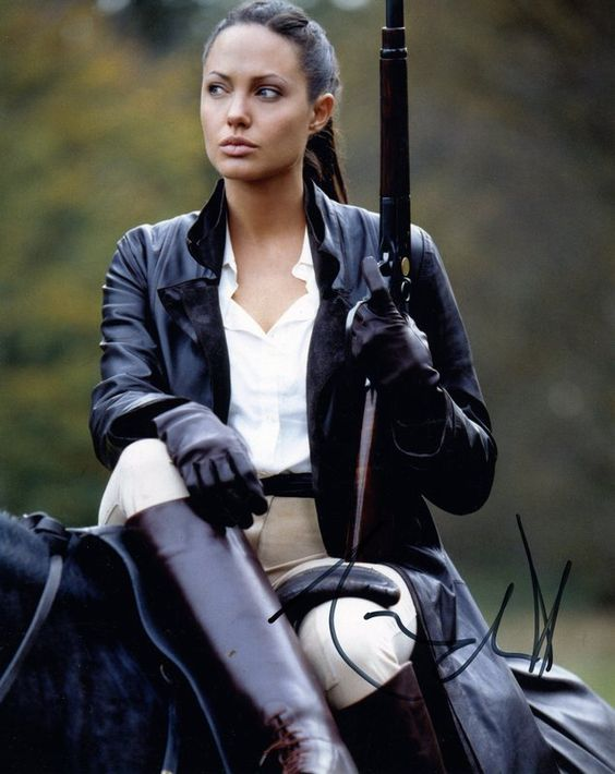 Angelina as lady lara croft combining equestrian leather and guns