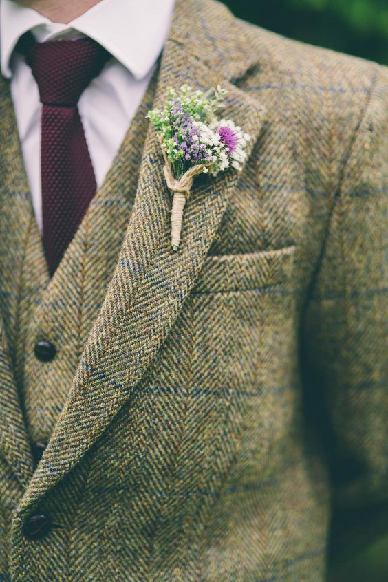 Wild flower button hole wrapped in twine complimenting the grooms tweed suit -   Image by  Neil  Jackson Photographic - A wedding in North Yorkshire with the bride in a blush pink vintage gown and the groom in tweed. Marquee wedding with paper flower arch and wild flowers.