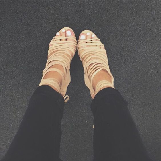 Tan strappy heels with light neutral nail polish
