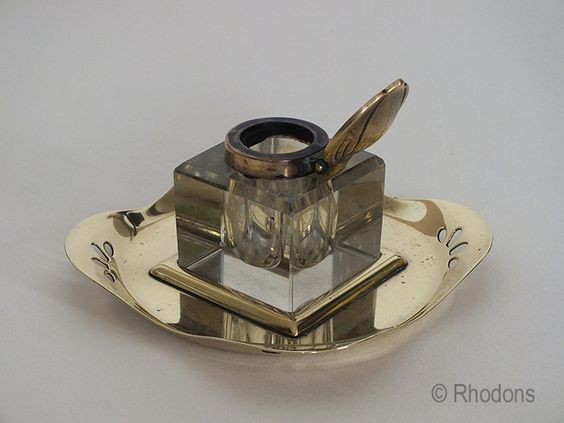Antique Glass Inkwell having a brass lid with Art Nouveau decoration and a pierced brass stand. Believed to date to the late Victorian / Edwardian era.