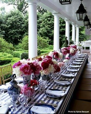 Chinoiserie Chic! Love the fuschia and pinks with the blue/white dishes and striped tablecover...