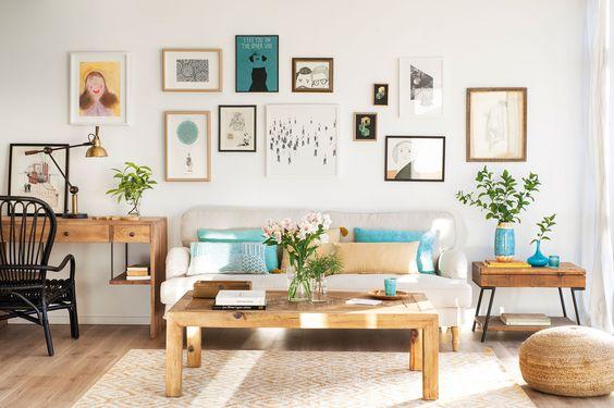 Salón con pared del sofá con composición de cuadros y láminas