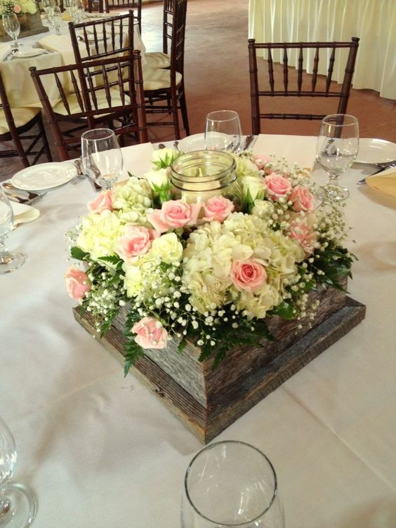 Barn wood box centerpiece with mason jar candle holder. White hydrangea, pink spray roses and baby's breath. Rustic wedding centerpieces by Chester's Flower Shop in Utica, NY