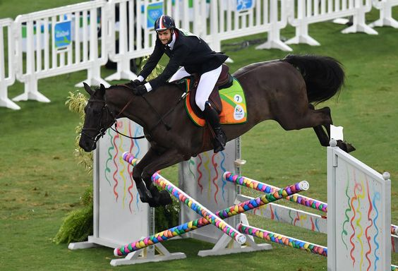France's Valentin Belaud crashes with his horse through an obstacle in the show jumping portion of the men's modern pentathlon event at the Deodoro Stadium during the Rio 2016 Olympic Games in Rio de Janeiro on August 20, 2016. / AFP / MANAN VATSYAYANA
