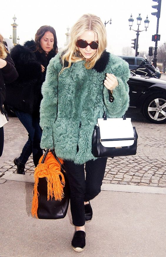Mary Kate Olsen wears a green fur coat and black cropped pants with oversized sunglasses, black espadrilles and two handbags.