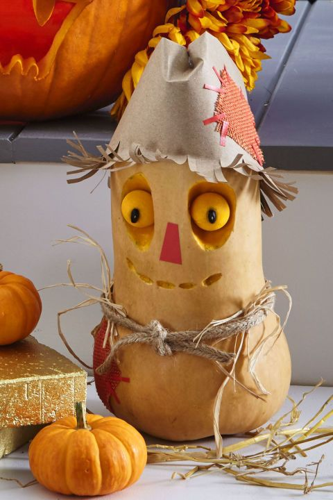 With a melon baller, scoop out two eyes from a butternut squash; reserve. Etch eye sockets and mouth with linoleum cutter. Use toothpicks to secure eyes in sockets. Push in black bean pupils. Cut masking tape and attach for nose. For hat, make a cone from a paper bag, then fold in its top and fringe its bottom, curling upward. Tie cord ribbon around middle for a belt and tuck in straw. Cut patches from burlap and attach with small masking tape strips.