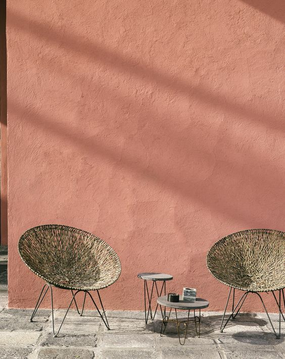 Comme pour rompre avec les lignes strictes de la maison, un salon en osier et ses petites tables vintage.