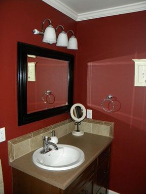 Red bathroom dark red walls dark wood trimmed mirror beige tile countertop for the home - Red bathroom color ideas ...