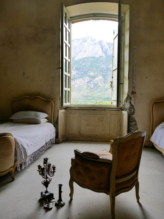 Classic French furniture in an aged to perfection bedroom with French windows open to the countryside. South of France Fixer Upper Château Gudanes. #southoffrance #frenchchateau #provence #frenchcountry #renovation