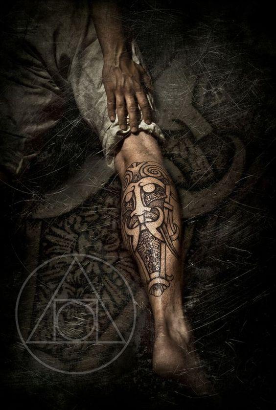 Visage viking en tatouage sur le mollet dans 20 motifs de l'art du tatouage viking pour homme par le créateur danois Peter Walrus Madsen