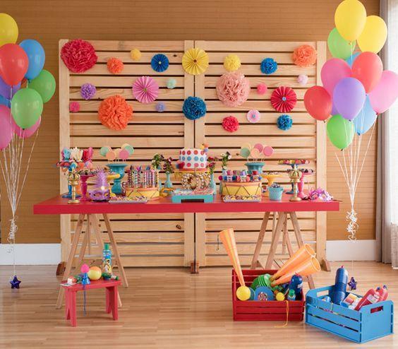 Decoração colorida para chá de bebê com balões coloridos, bolo, painel de madeira feita a base de pallets, caixa de pallets coloridos.