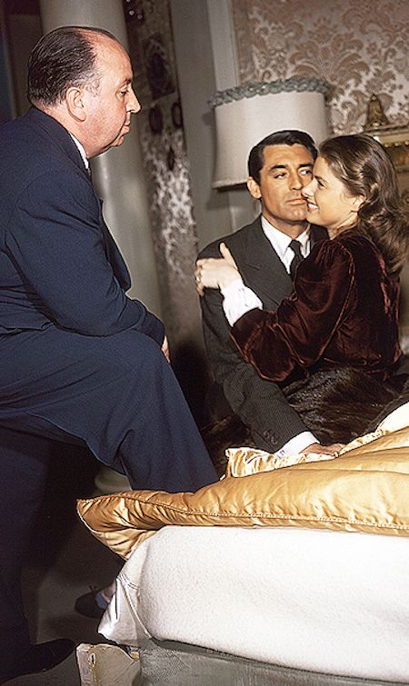 Cary Grant and Ingrid Bergman are directed by Alfred Hitchcock on the set of…