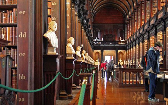 """The Trinity College Library is the largest library in Dublin, and fulfills many of the same functions for Ireland that the Library of Congress fulfills for the US. It actually consists of four separate buildings, but we are concerned here with the old Trinity College Library, built in 1732. The """"Long Room"""" in the Old Library is one of Ireland's biggest tourist draws and houses the Book of Kells (a beautiful Gospel book created by Celtic monks roughly around 800) and many other very early…"""