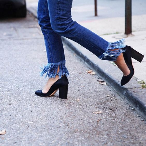 Cropped fringe jeans are paired with black pumps