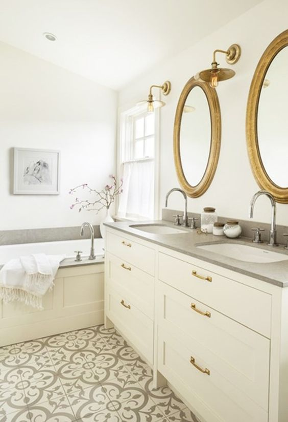 Bathroom with round mirrors, gray and white patterned encaustic tile floor, cement countertop designed by Sophie Burke, via @sarahsarna.: